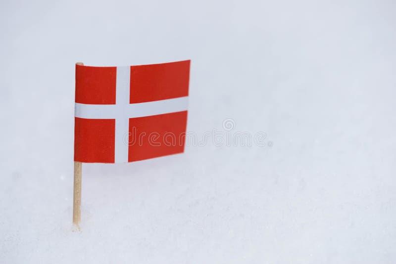 Bandeira de Dinamarca feita do papel com o palito marrom no fundo branco da neve foto de stock royalty free