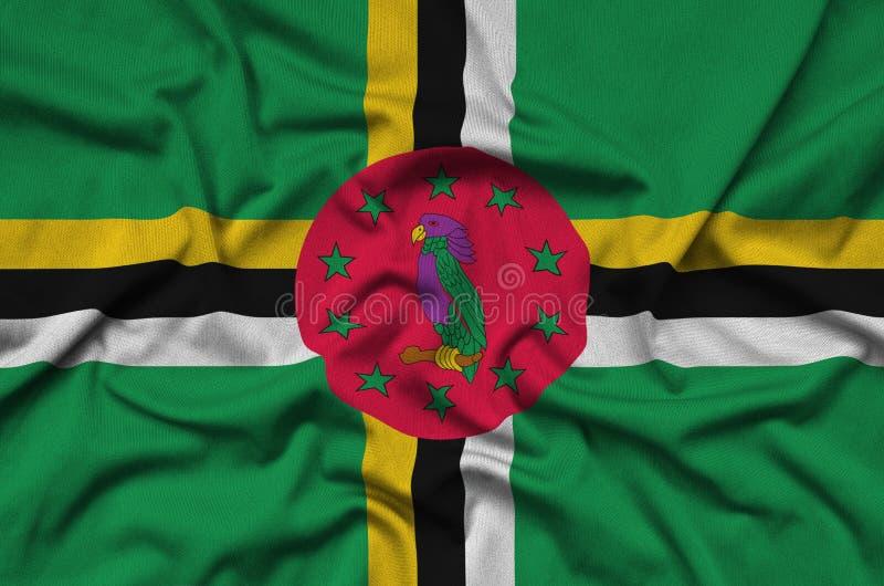 A bandeira de Domínica é descrita em uma tela de pano dos esportes com muitas dobras Bandeira da equipe de esporte imagem de stock royalty free