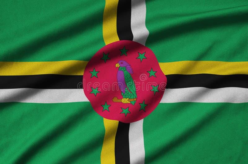 A bandeira de Domínica é descrita em uma tela de pano dos esportes com muitas dobras Bandeira da equipe de esporte imagem de stock