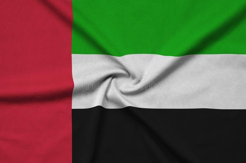 A bandeira de Emiratos Árabes Unidos é descrita em uma tela de pano dos esportes com muitas dobras Bandeira da equipe de esporte foto de stock