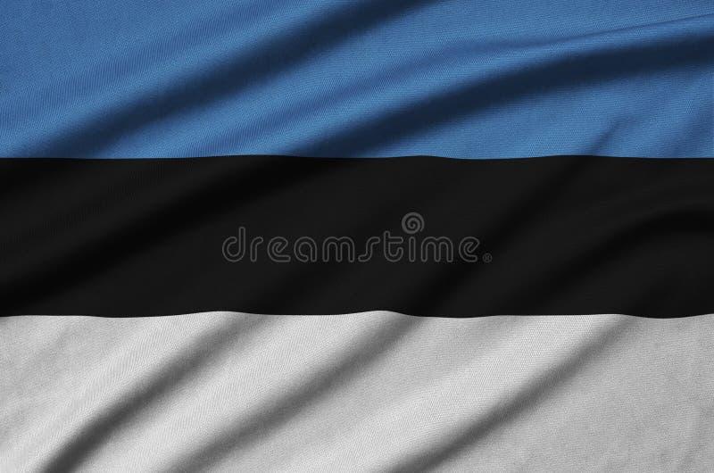 A bandeira de Estônia é descrita em uma tela de pano dos esportes com muitas dobras Bandeira da equipe de esporte fotografia de stock royalty free