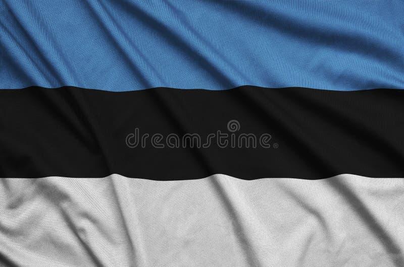A bandeira de Estônia é descrita em uma tela de pano dos esportes com muitas dobras Bandeira da equipe de esporte foto de stock