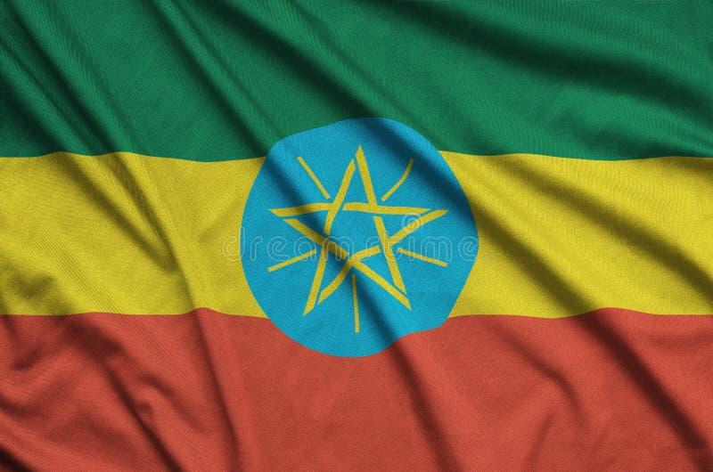 A bandeira de Etiópia é descrita em uma tela de pano dos esportes com muitas dobras Bandeira da equipe de esporte imagens de stock royalty free