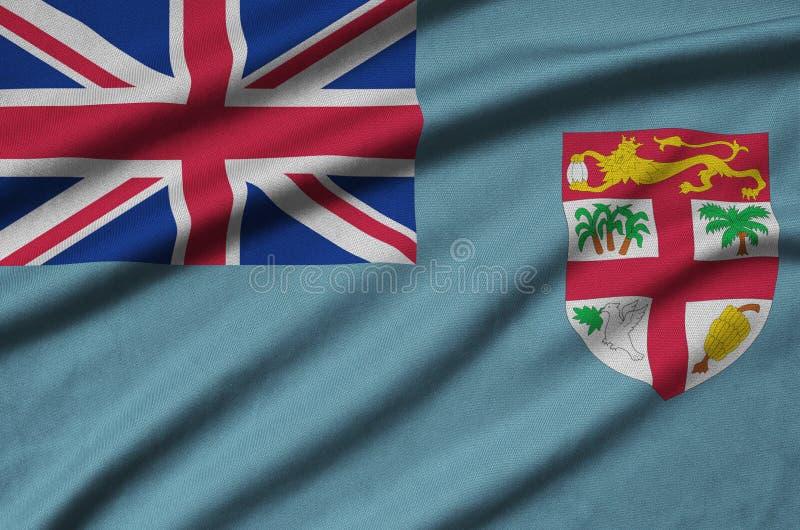 A bandeira de Fiji é descrita em uma tela de pano dos esportes com muitas dobras Bandeira da equipe de esporte imagens de stock royalty free