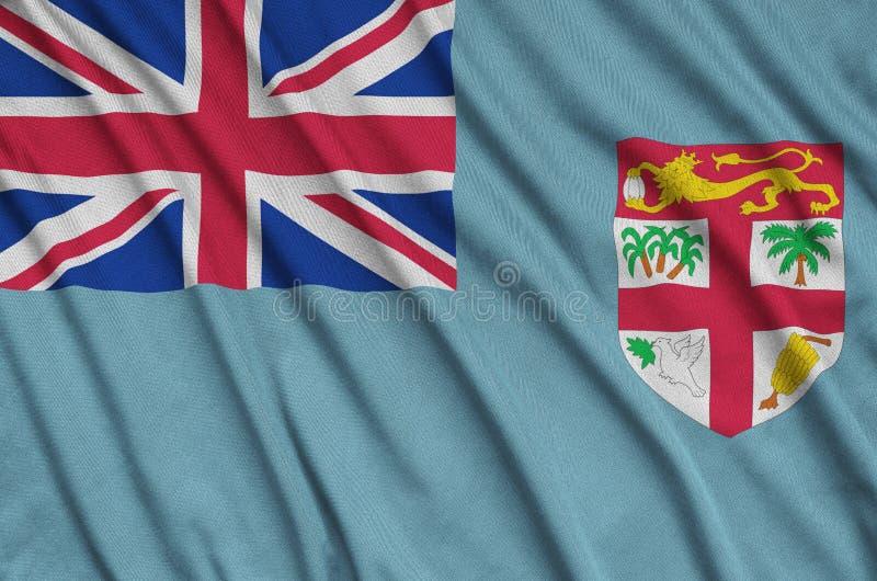 A bandeira de Fiji é descrita em uma tela de pano dos esportes com muitas dobras Bandeira da equipe de esporte imagem de stock
