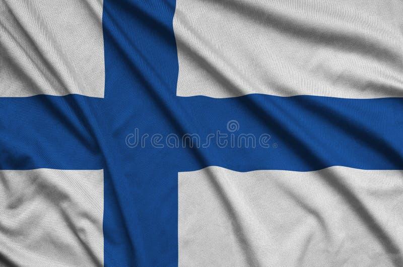 A bandeira de Finlandia é descrita em uma tela de pano dos esportes com muitas dobras Bandeira da equipe de esporte imagens de stock royalty free