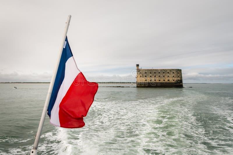 A bandeira de france com uma fortaleza do mar no fundo foto de stock