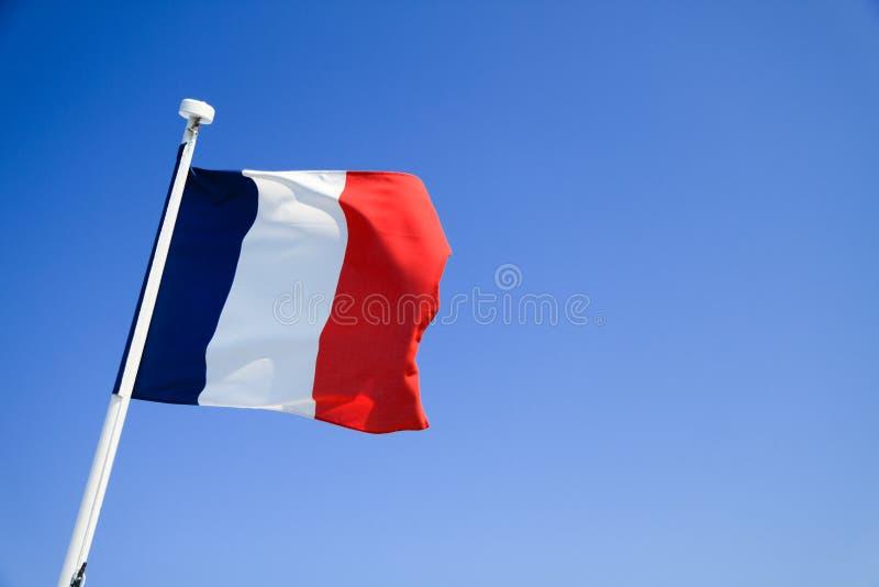 Bandeira de France que acena com o céu azul claro imagens de stock royalty free