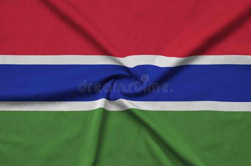 A bandeira de Gâmbia é descrita em uma tela de pano dos esportes com muitas dobras Bandeira da equipe de esporte imagem de stock royalty free
