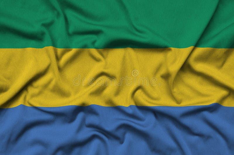 A bandeira de Gabão é descrita em uma tela de pano dos esportes com muitas dobras Bandeira da equipe de esporte fotos de stock