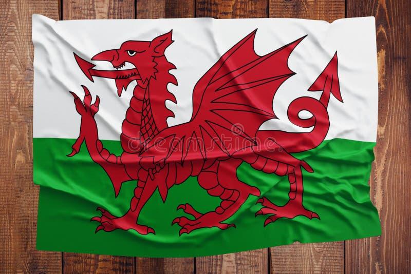 Bandeira de Gales em um fundo de madeira da tabela Opini?o superior enrugada da bandeira de Galler foto de stock royalty free