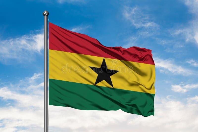 Bandeira de Gana que acena no vento contra o céu azul nebuloso branco Bandeira ganesa fotografia de stock