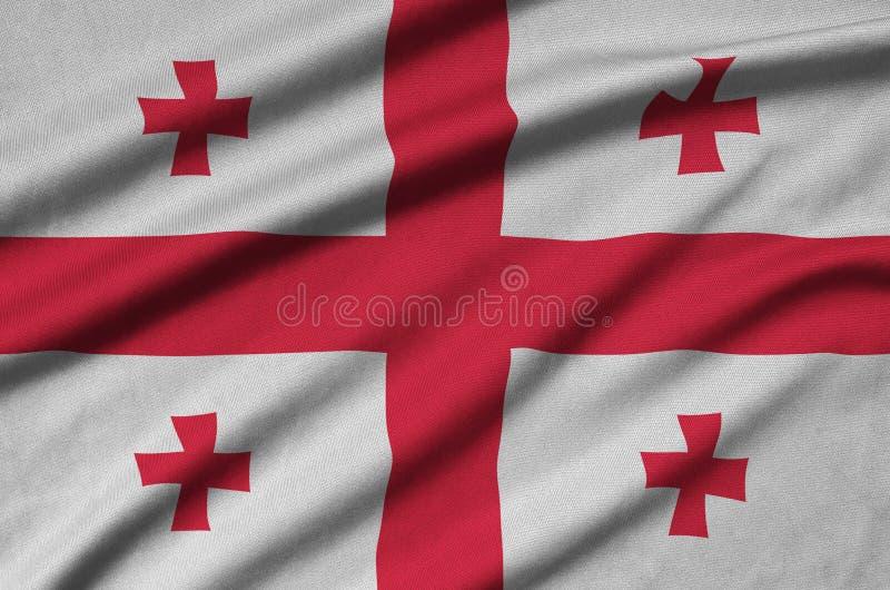 A bandeira de Geórgia é descrita em uma tela de pano dos esportes com muitas dobras Bandeira da equipe de esporte imagem de stock royalty free