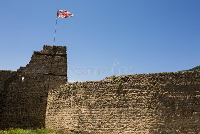 Bandeira de Geórgia que torna-se na fortaleza arruinada na cidade de Mtskheta foto de stock royalty free
