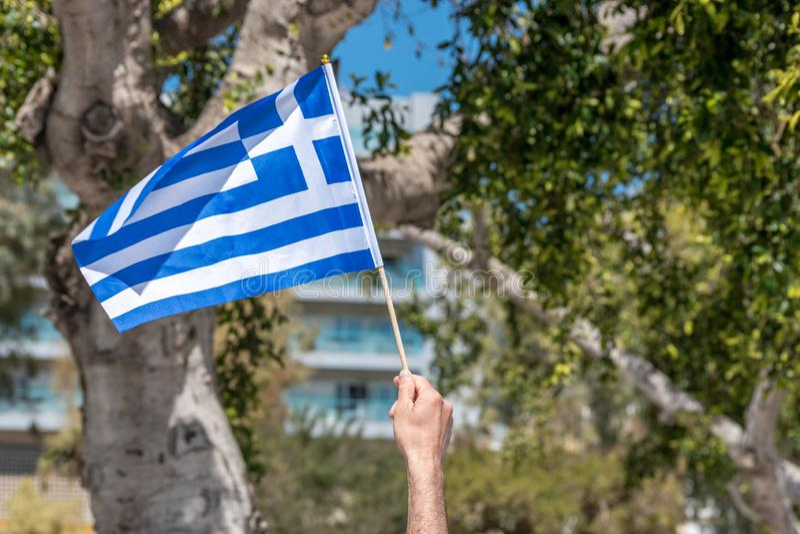 Bandeira de Grécia na mão humana no fundo das árvores imagem de stock royalty free