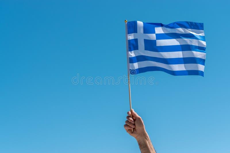 Bandeira de Grécia na mão humana no fundo do céu fotografia de stock royalty free