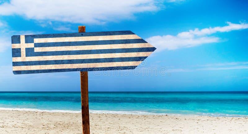 Bandeira de Grécia no sinal de madeira da tabela no fundo da praia É sinal do verão de Grécia ilustração royalty free