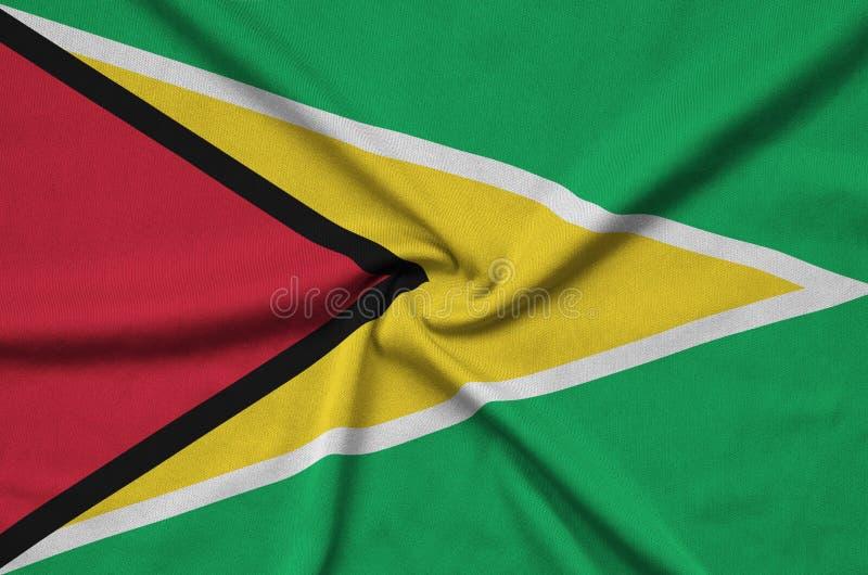 A bandeira de Guiana é descrita em uma tela de pano dos esportes com muitas dobras Bandeira da equipe de esporte fotos de stock royalty free