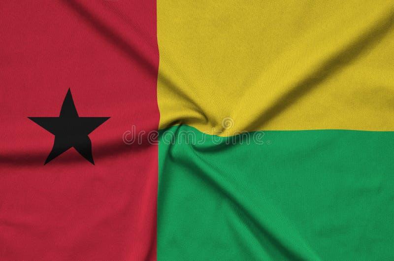 A bandeira de Guiné-Bissau é descrita em uma tela de pano dos esportes com muitas dobras Bandeira da equipe de esporte fotografia de stock royalty free