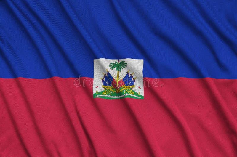 A bandeira de Haiti é descrita em uma tela de pano dos esportes com muitas dobras Bandeira da equipe de esporte imagens de stock royalty free