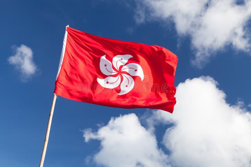 Bandeira de Hong Kong que acena sobre o céu nebuloso azul fotografia de stock