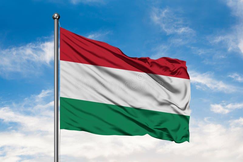 Bandeira de Hungria que acena no vento contra o céu azul nebuloso branco Bandeira h?ngara foto de stock