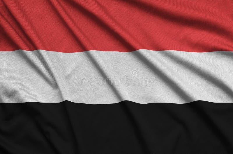 A bandeira de Iémen é descrita em uma tela de pano dos esportes com muitas dobras Bandeira da equipe de esporte imagem de stock
