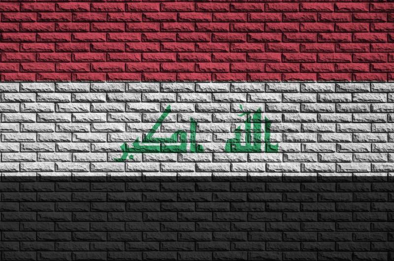 A bandeira de Iraque é pintada em uma parede de tijolo velha foto de stock