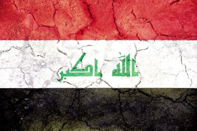 Bandeira de Iraque pintada em terra rachada foto de stock royalty free