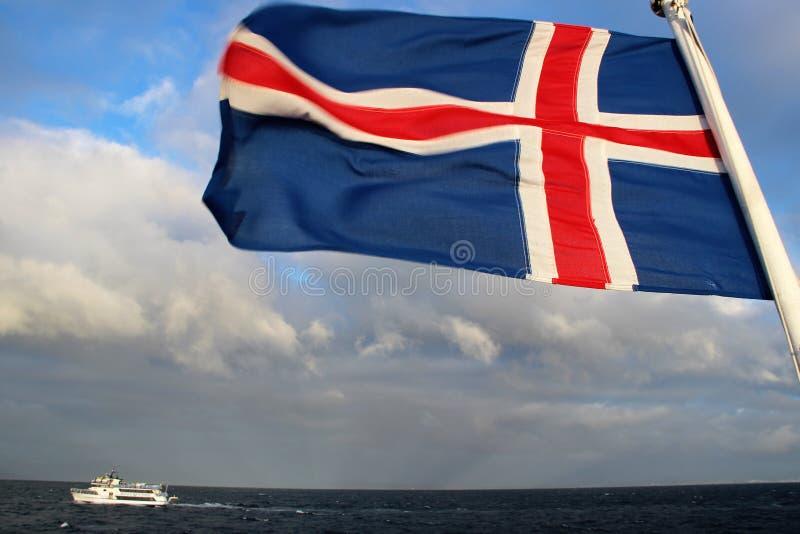 A bandeira de Islândia voa sobre o oceano fotografia de stock royalty free