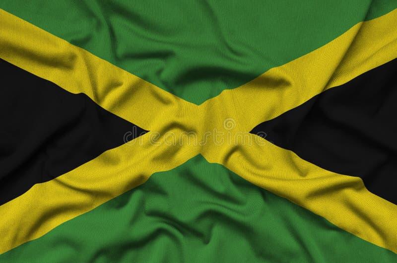A bandeira de Jamaica é descrita em uma tela de pano dos esportes com muitas dobras Bandeira da equipe de esporte imagens de stock