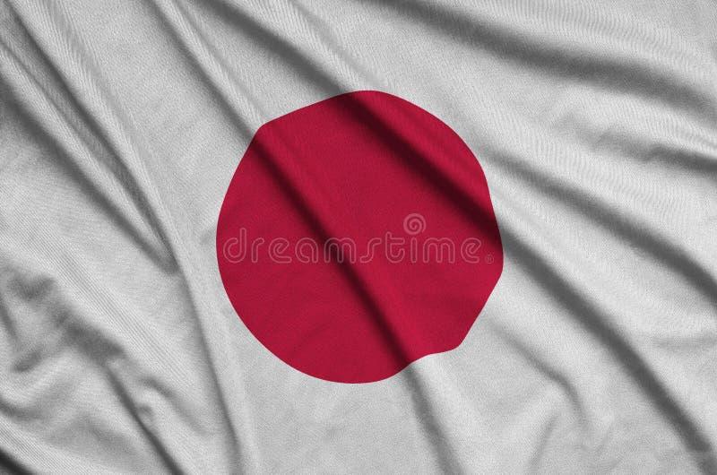 A bandeira de Japão é descrita em uma tela de pano dos esportes com muitas dobras Bandeira da equipe de esporte foto de stock royalty free