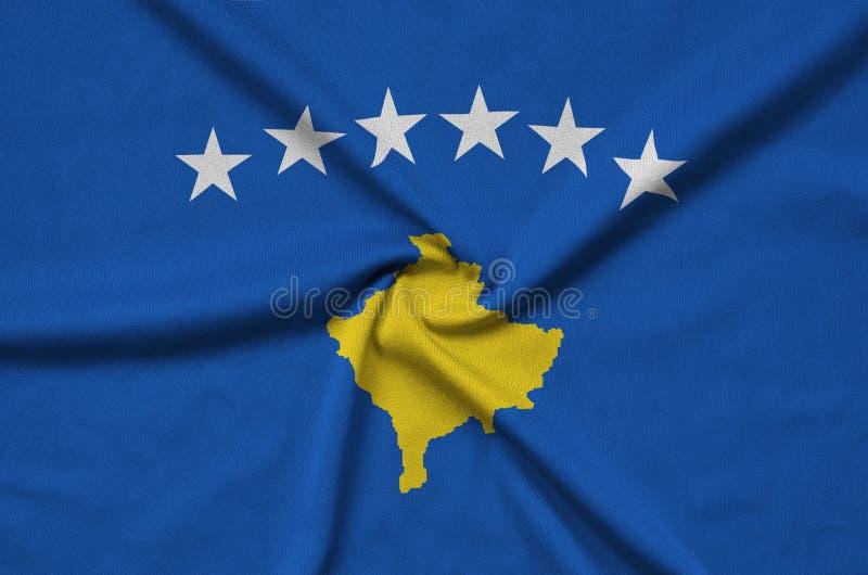 A bandeira de Kosovo é descrita em uma tela de pano dos esportes com muitas dobras Bandeira da equipe de esporte fotografia de stock royalty free