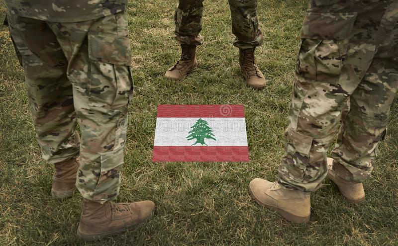 Bandeira de Líbano e de pés dos soldados na colagem da grama foto de stock