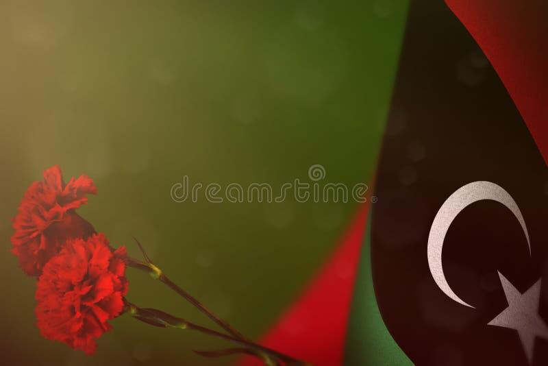 Bandeira de Líbia para a honra dos veteranos ou o Memorial Day com as duas flores vermelhas do cravo Glória aos heróis de Líbia d fotografia de stock royalty free