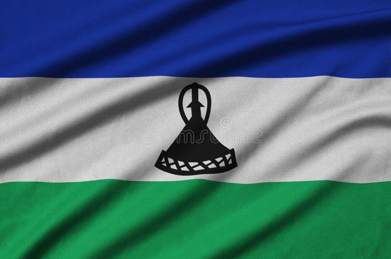 A bandeira de Lesoto é descrita em uma tela de pano dos esportes com muitas dobras Bandeira da equipe de esporte imagens de stock royalty free