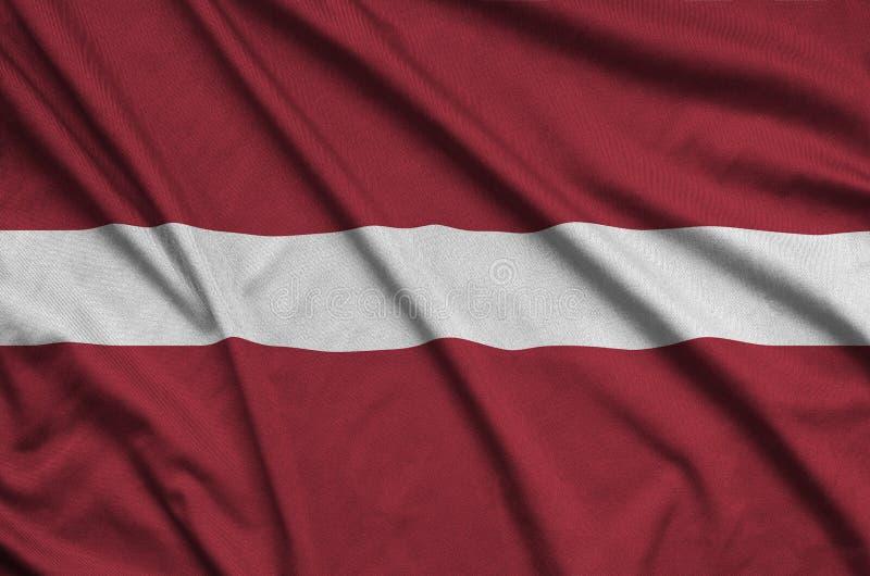 A bandeira de Letónia é descrita em uma tela de pano dos esportes com muitas dobras Bandeira da equipe de esporte imagens de stock royalty free