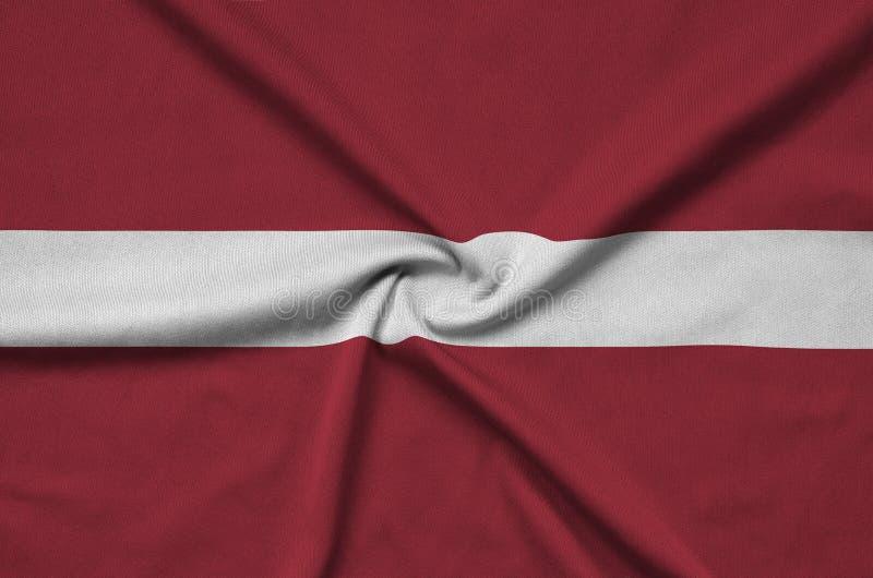 A bandeira de Letónia é descrita em uma tela de pano dos esportes com muitas dobras Bandeira da equipe de esporte imagem de stock