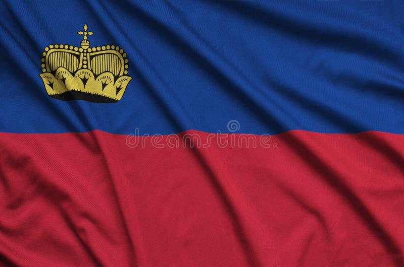 A bandeira de Liechtenstein é descrita em uma tela de pano dos esportes com muitas dobras Bandeira da equipe de esporte fotografia de stock