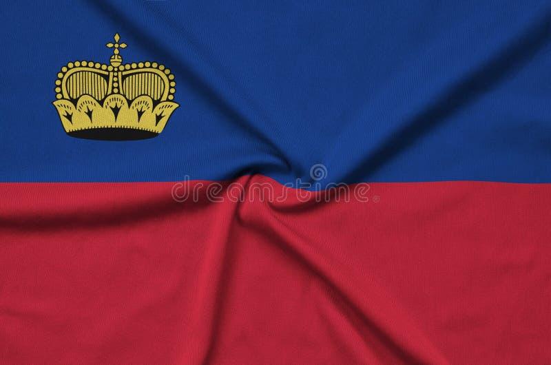 A bandeira de Liechtenstein é descrita em uma tela de pano dos esportes com muitas dobras Bandeira da equipe de esporte fotografia de stock royalty free