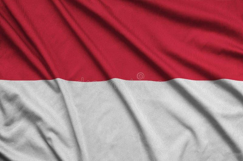 A bandeira de Mônaco é descrita em uma tela de pano dos esportes com muitas dobras Bandeira da equipe de esporte imagem de stock