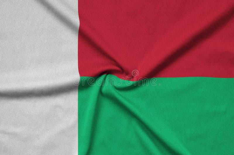 A bandeira de Madagáscar é descrita em uma tela de pano dos esportes com muitas dobras Bandeira da equipe de esporte fotografia de stock royalty free