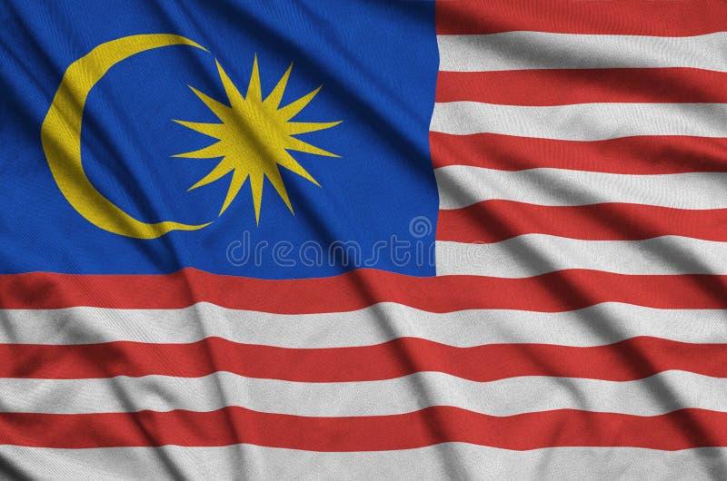 A bandeira de Malásia é descrita em uma tela de pano dos esportes com muitas dobras Bandeira da equipe de esporte foto de stock royalty free