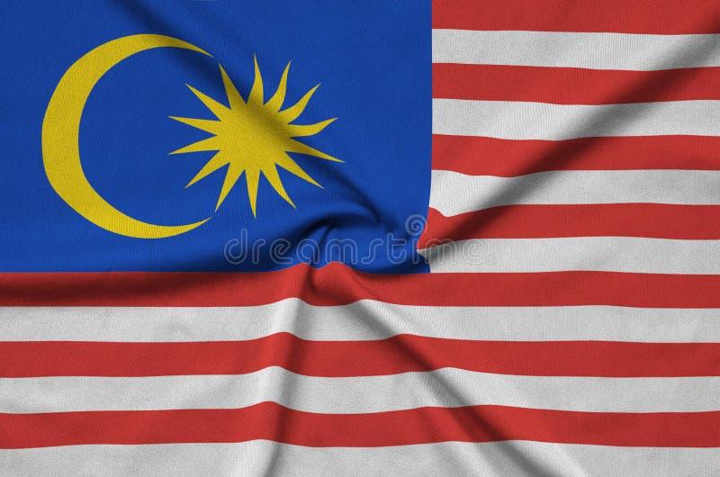 A bandeira de Malásia é descrita em uma tela de pano dos esportes com muitas dobras Bandeira da equipe de esporte foto de stock