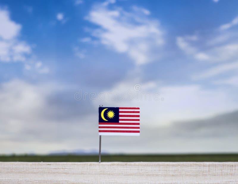Bandeira de Malásia com prado vasto e o céu azul atrás dele fotografia de stock royalty free