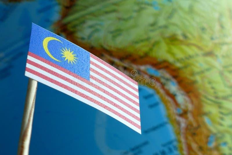 Bandeira de Malásia com um mapa do globo como um fundo imagem de stock royalty free