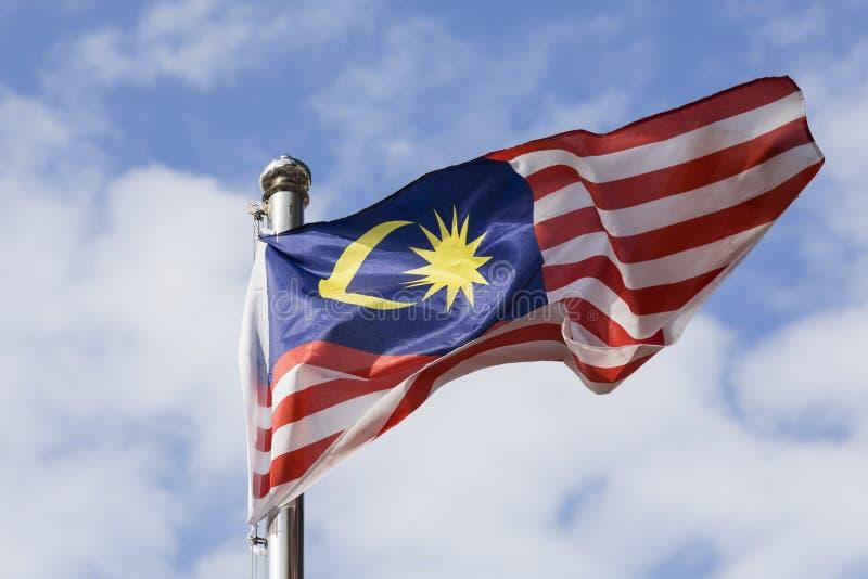 Bandeira de Malásia igualmente conhecida como a onda de Jalur Gemilang com o céu azul imagens de stock