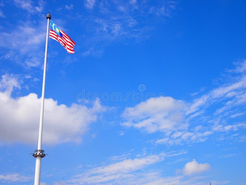 Bandeira de Malásia que acena no vento com céu azul fotografia de stock