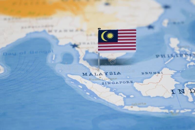 A bandeira de malaysia no mapa do mundo imagem de stock