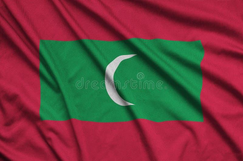 A bandeira de Maldivas é descrita em uma tela de pano dos esportes com muitas dobras Bandeira da equipe de esporte fotografia de stock royalty free